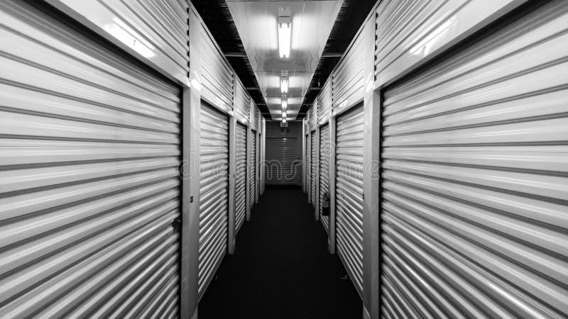 Portes noires et blanches d'unité de stockage d'individu en métal de chaque côté d'un couloir image libre de droits