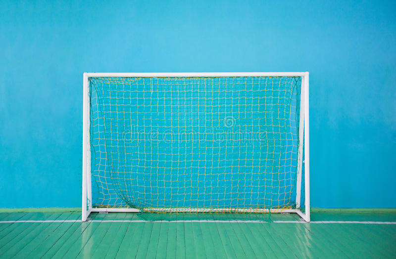 Portes pour le mini-football sur le fond du mur bleu image stock