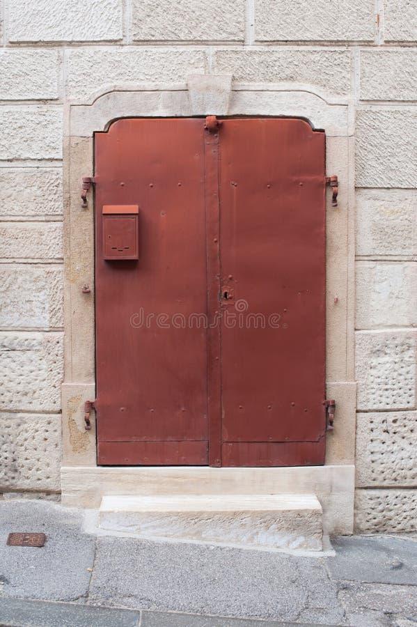 Portes rouges vieil en métal dans un mur en pierre, maison Portes rouges en métal avec la petite boîte aux lettres Conception ext photos libres de droits
