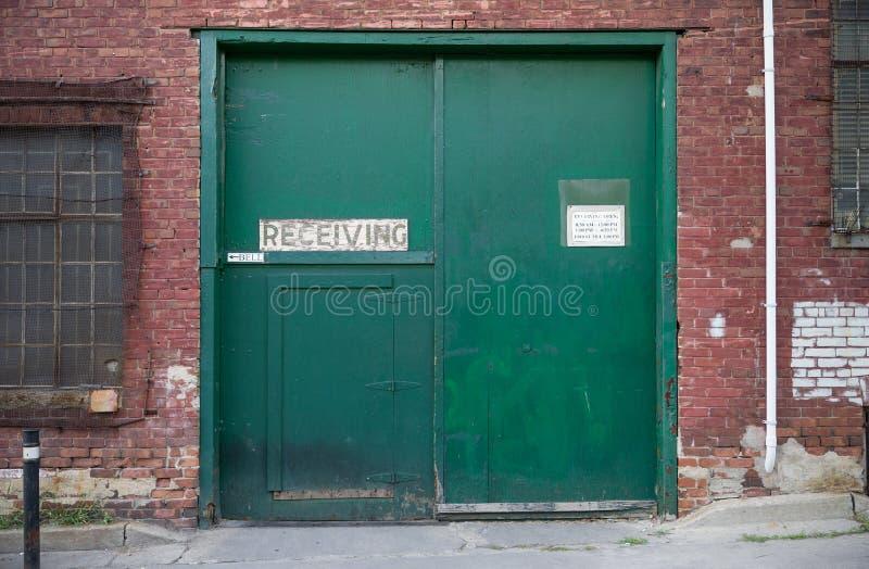 Portes vertes d'un entrepôt recevant l'entrée images stock