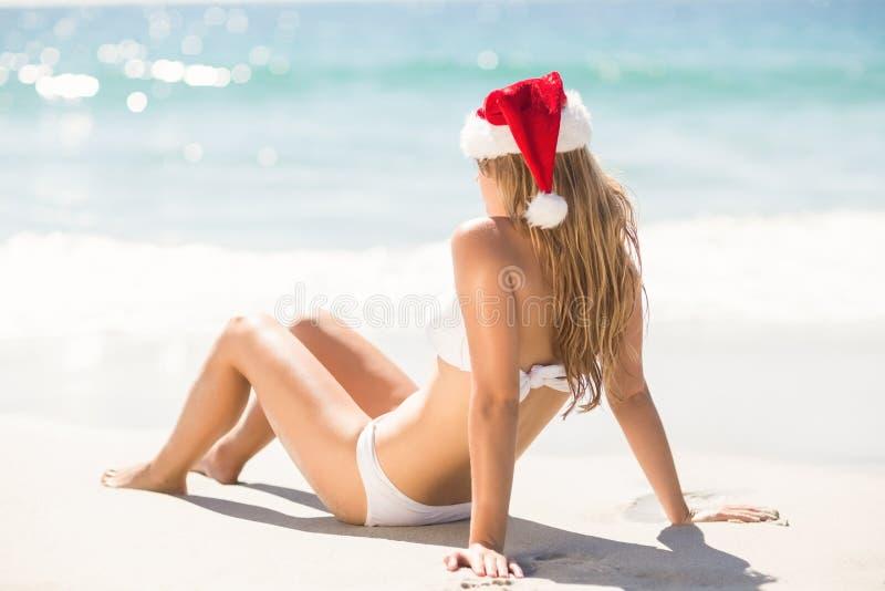 Portez la vue de la femme blonde regardant la mer avec le chapeau du père noël photos stock