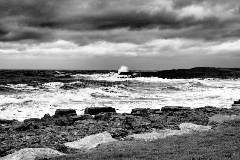 Porthcawl on a stormy day with waves crashing onto rocks, shot in monochrome, South Wales. Porthcawl on a dramatic stormy day with waves crashing onto rocks royalty free stock photo