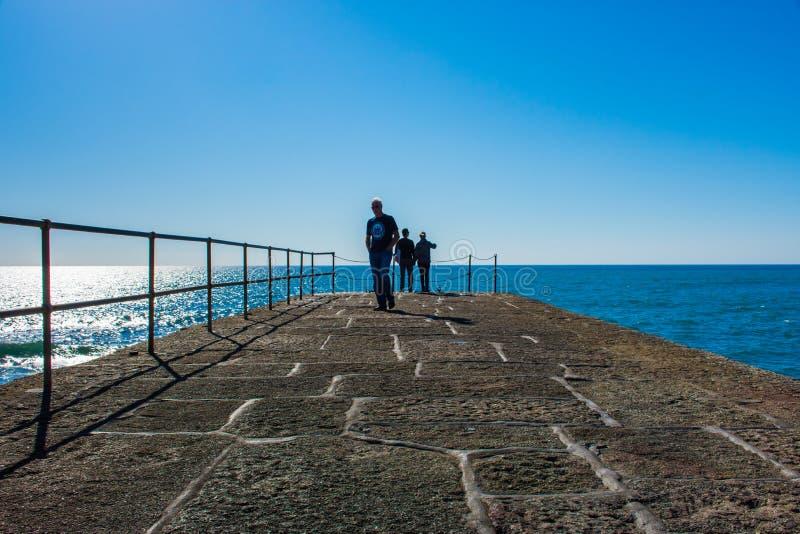 Porthlevenpijler met toerist die op de oceaan letten stock afbeelding