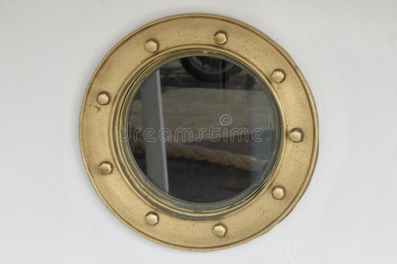Porthole at a ship - brass frame. Porthole or bull`s eye with brass frame and screws at a ship royalty free stock image