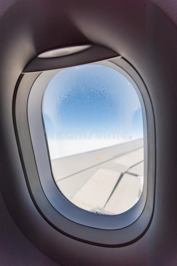 Porthole view inside. Airplane porthole view into open space sky royalty free stock photo