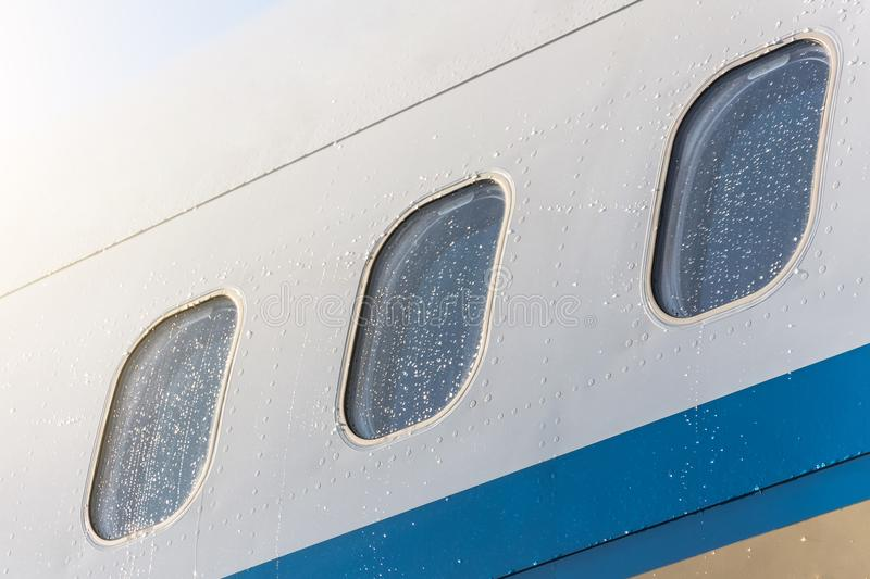 Porthole windows of an airplane wet weather in rain drops of water, close-up. royalty free stock photos