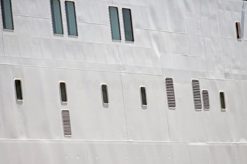 Portholes in the white hull of ship stock image