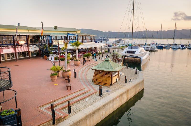 Porticciolo del porto del centro urbano di Knysna al tramonto ed ai ristoranti, itinerario del giardino, Sudafrica, fotografia stock libera da diritti