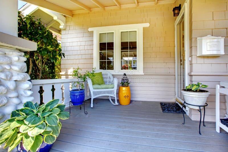 Portico coperto dell'entrata con le piante e la presidenza. immagine stock