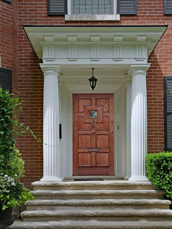 Portico entrance of brick house with large white columns royalty free stock photography