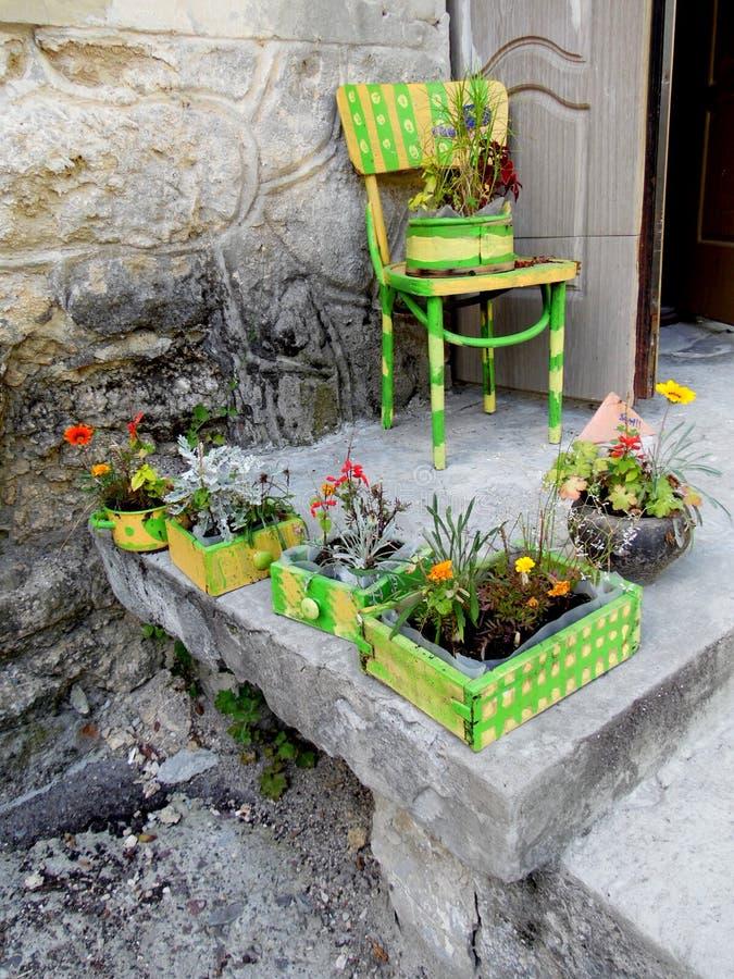 Portico piacevole della casa con i letti di fiore dipinti e una sedia fotografie stock libere da diritti