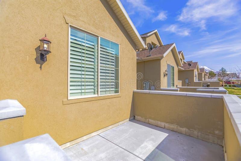 Portiek die andere huizen en sneeuwberg overzien onder blauwe hemel op een zonnige dag stock fotografie