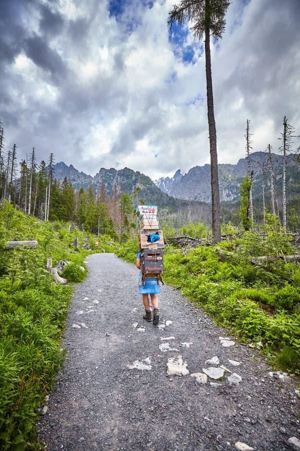 Portier de montagne portant les approvisionnements alimentaires lourds à une de huttes de montagne photographie stock