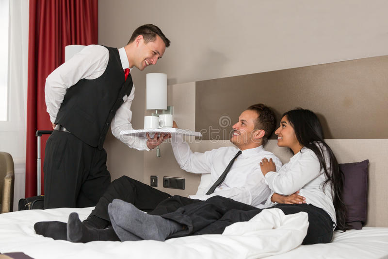 Portier dienende koffie aan gasten in een hotelruimte stock foto