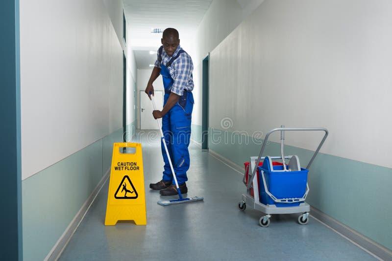 Portier masculin Mopping In Corridor images libres de droits