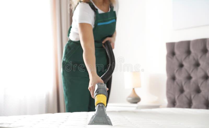 Portier schoonmakende matras met beroepsuitrusting in slaapkamer, stock afbeelding