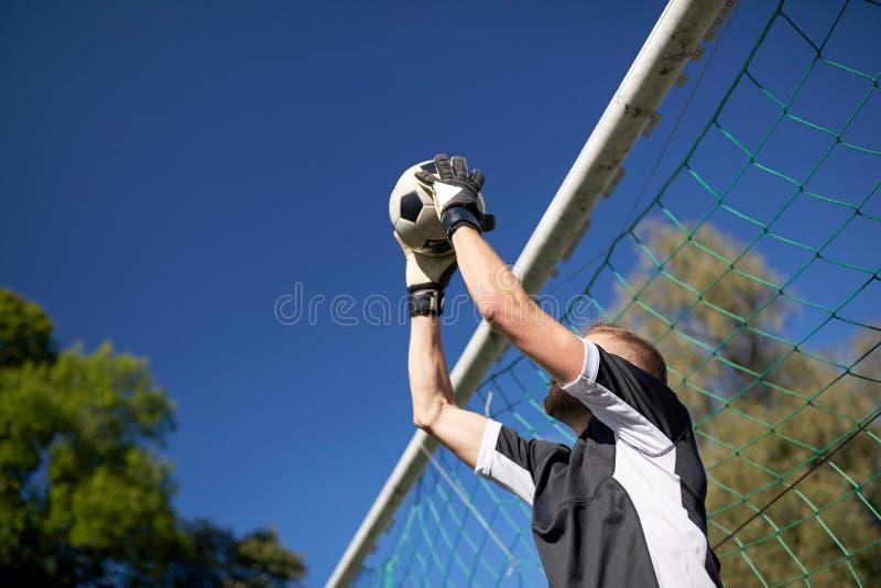 Portiere con la palla allo scopo di calcio sul campo immagini stock libere da diritti