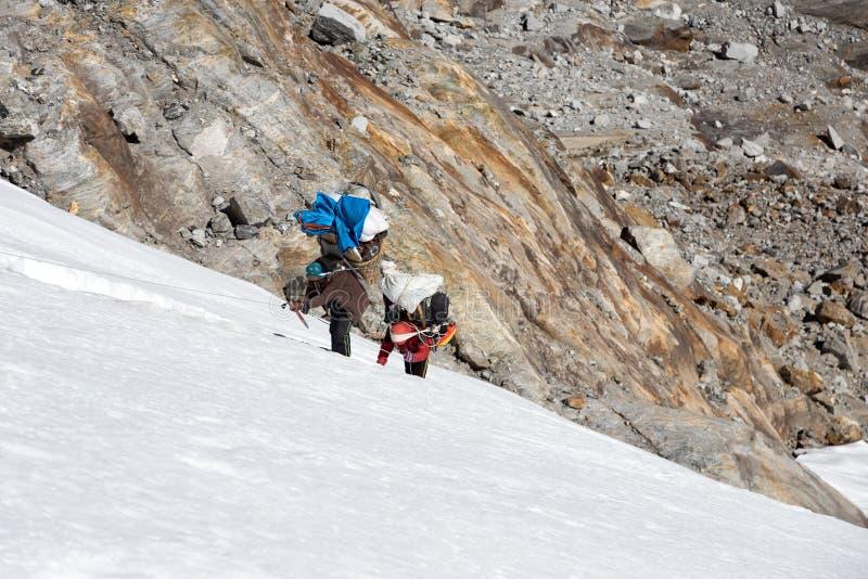 Portiers népalais de montagne montant le glacier sur le mur raide de glace photo stock
