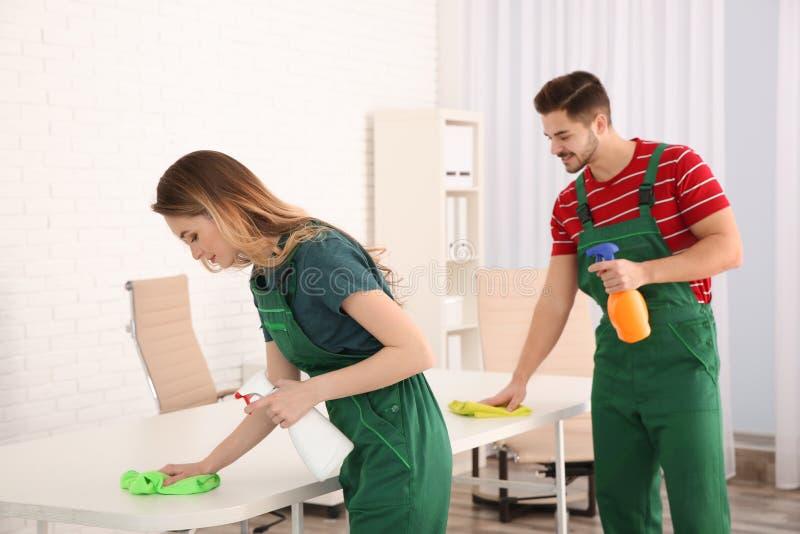 Portiers professionnels nettoyant la table dans le bureau image stock