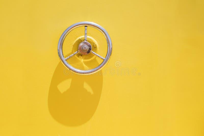 Portilla de la rueda en puerta amarilla del buque foto de archivo
