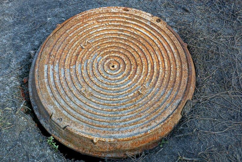 Portilla oxidada vieja de la alcantarilla en el camino en la tierra fotos de archivo