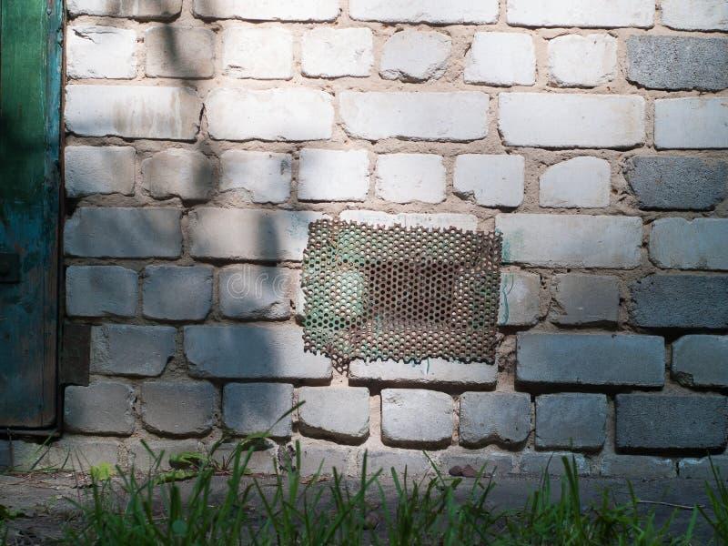 Portilla oxidada vieja del metal en pared de ladrillo vieja imágenes de archivo libres de regalías