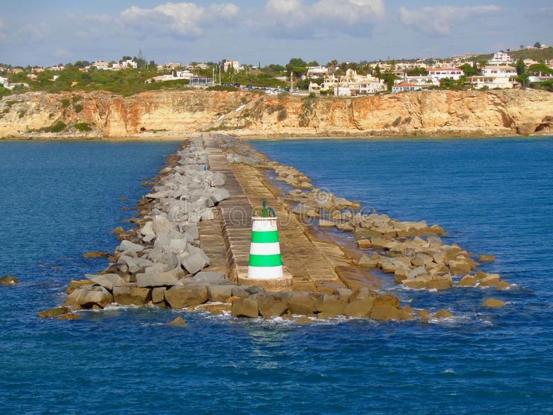 Portimao, Portugal coastline view. The seawall protects  the harbor area in Portimao, Portugal. The image was shot from a cruise ship departing the harbor royalty free stock photo