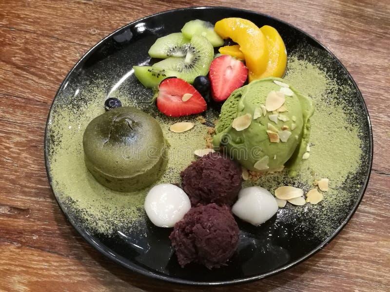 Portion caoutchouteuse molle de gâteau de lave de thé vert et de glace de thé vert avec la fraise fraîche, le kiwi, la pêche et l images libres de droits