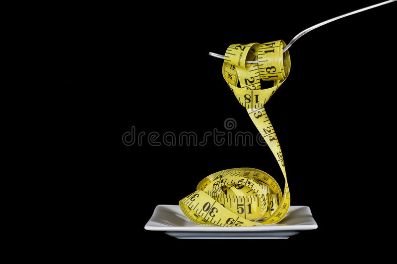 Portion Control. Conceptual image depicting weight loss through portion control utilizing a tape measure and fork against black background stock photography