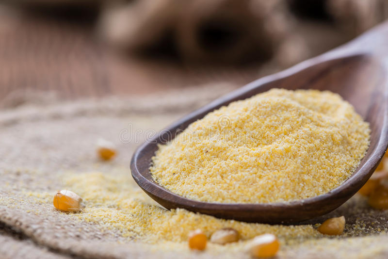 Portion of Cornmeal. Portion of fresh Cornmeal (close-up shot) on rustic wooden background royalty free stock photos