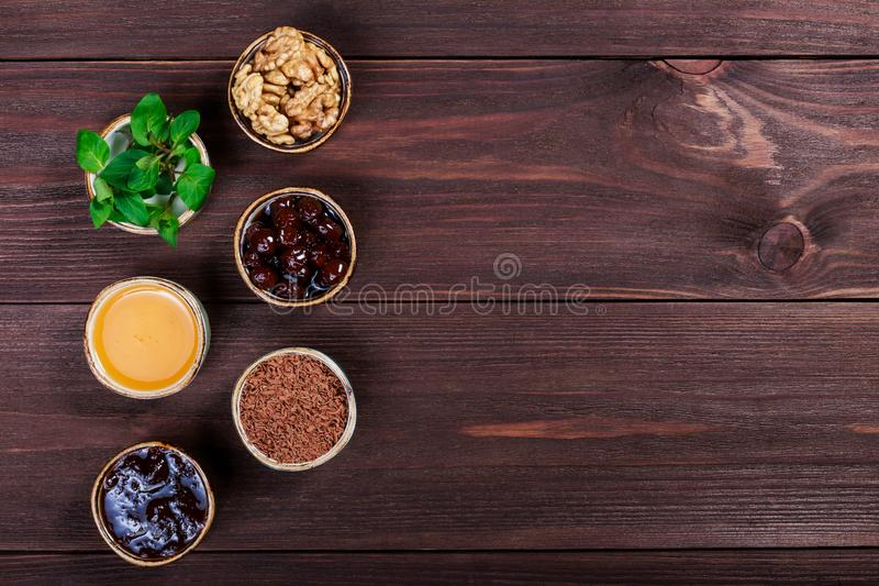 Portion cups of healthy ingredients on dark wooden table, jam, honey, mint, grated chocolate, cherry jam, walnuts. Top view royalty free stock photos