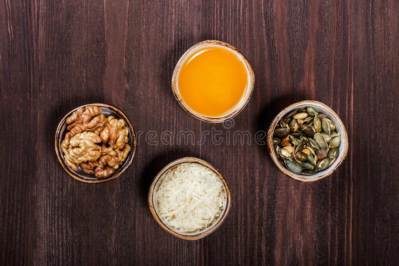 Portion cups of healthy sweet ingredients on dark wooden table, fried pumpkin seeds, grated parmesan cheese, honey, walnuts. royalty free stock photography