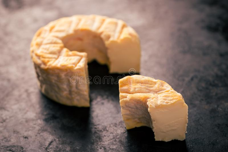 Portion cut from whole camembert cheese with orange color. Horizontal photo of whole special camembert cheese with golden color and hole in the middle with cut stock images