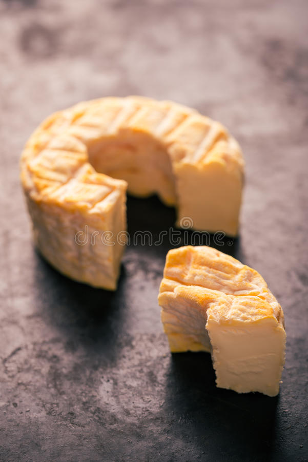 Portion cut from whole golden camembert cheese on dark tray. Vertical photo of whole special camembert cheese with golden color and hole in the middle with cut royalty free stock images