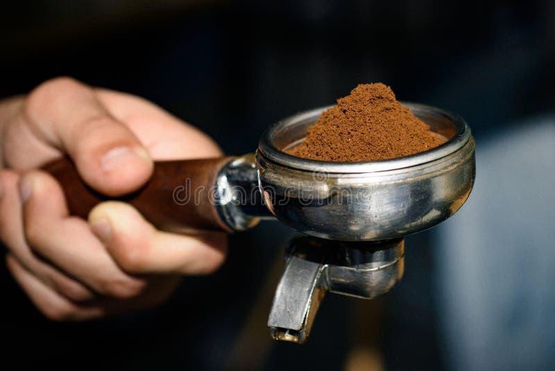 Portion de cafè moulu pur nouvellement fabriqué À café dans le café Portafilter de prise de barman à disposition brassage images libres de droits