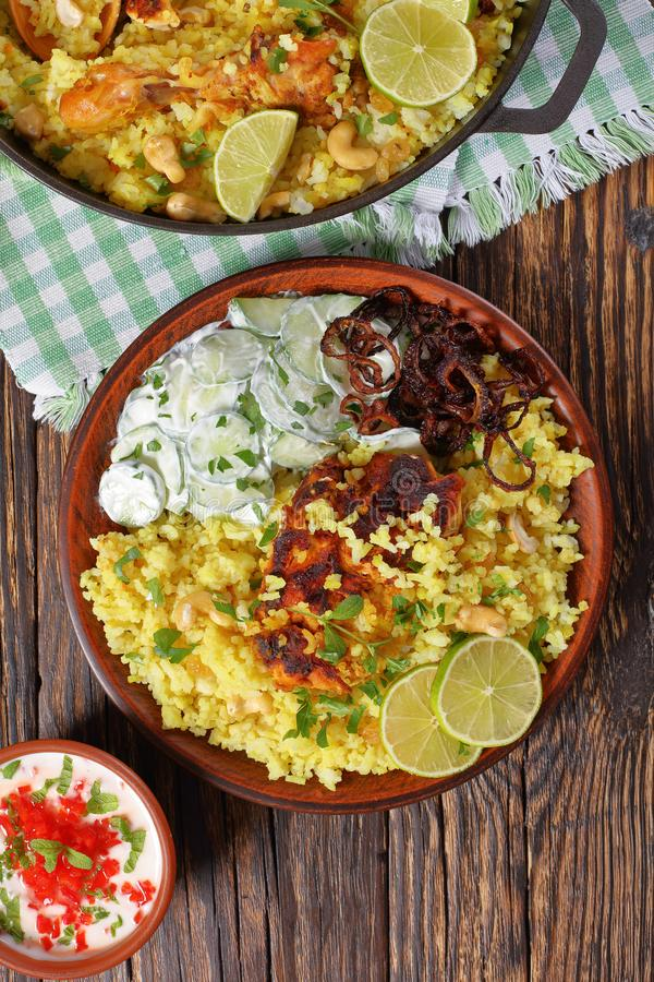 Portion of a delicious chicken biryani. Portion of delicious chicken biryani or indian spicy chicken pilau served on clay plate with cucumber yogurt raita, lime stock images