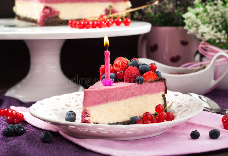 Portion of delicious raspberry cheesecake. Decorated with fresh berries, chocolate and candle royalty free stock images