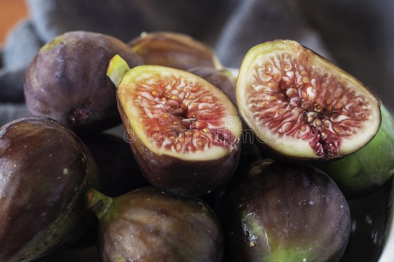 Portion of fresh Figs in close up. Whole figs and one fig sliced in half, close up royalty free stock photography