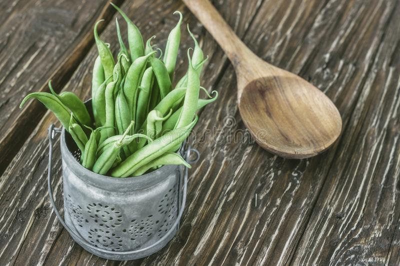 Portion of fresh green beans and spoon on a wooden background royalty free stock image