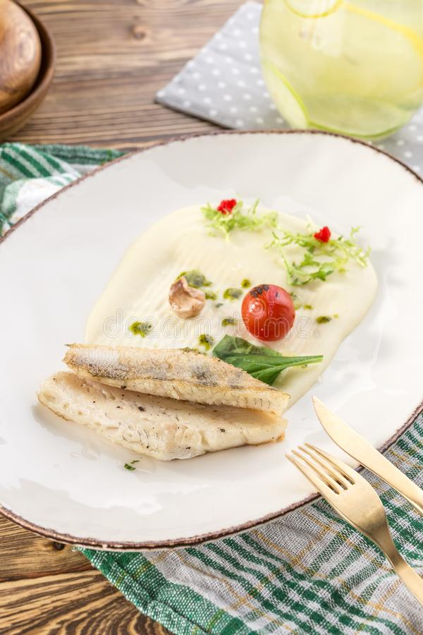 Portion of golden fried sea fish served on white plate with mashed potato and tomato on wooden table stock image