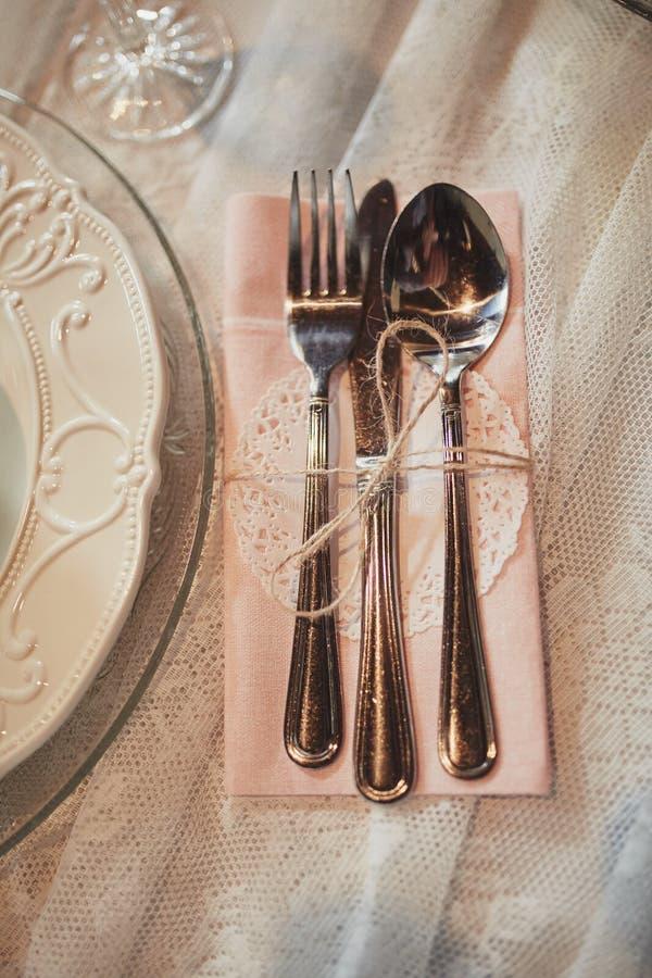 Portion inställningstabell plattor och servetten för bestickbesticklinne dekoreras med band bröllop för tabell för pargarneringdo royaltyfria bilder