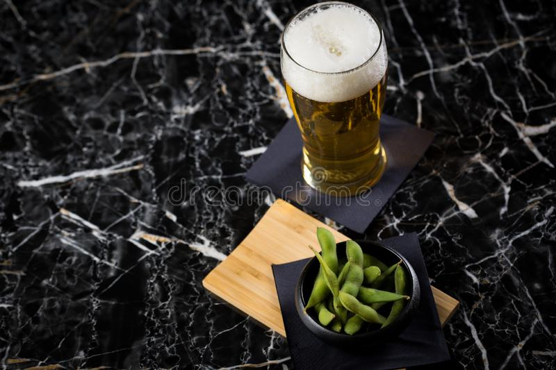 Portion Japanese Edamame soy beans in porcelain bowl on wooden board with beer glass on napkin and black marble background stock photo