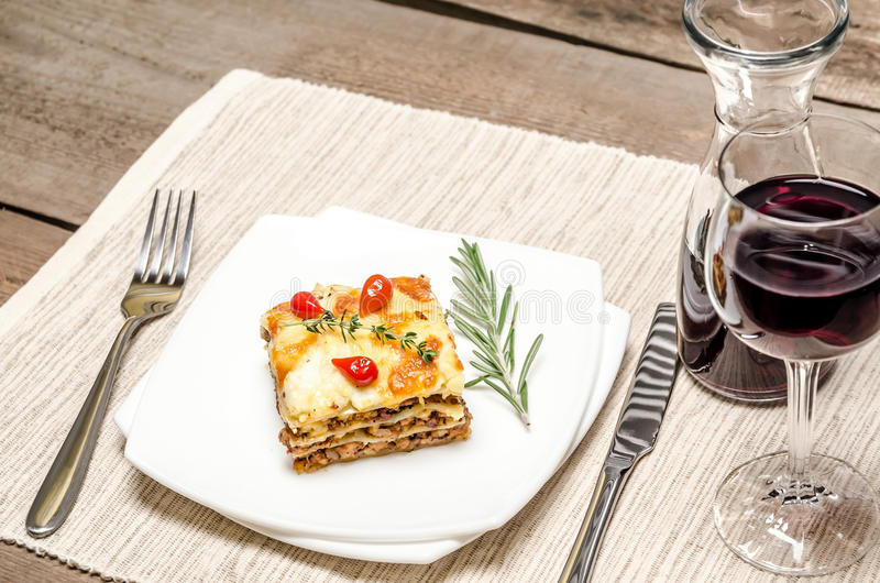 Portion of lasagna on the wooden table stock photography