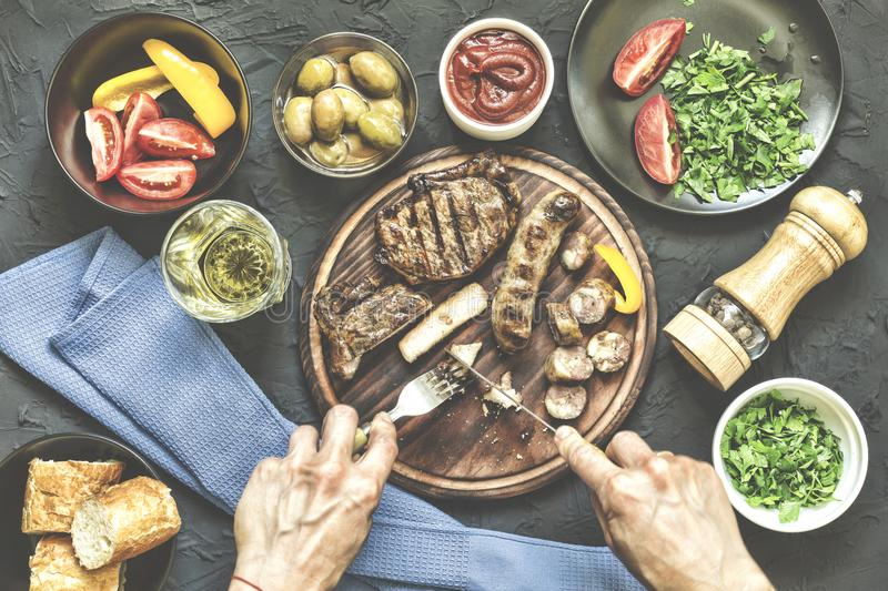 Portion lunch. A la carte lunch. Fresh vegetables, a barbecue steak and various snacks.Man eats a juicy barbecue steak. Top view royalty free stock photo