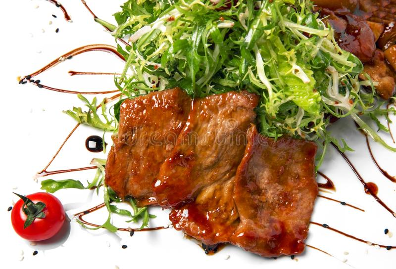 Meat in sauce and greens on a white plate royalty free stock images