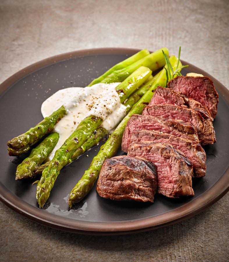 Portion of sliced beef steak and asparagus royalty free stock image