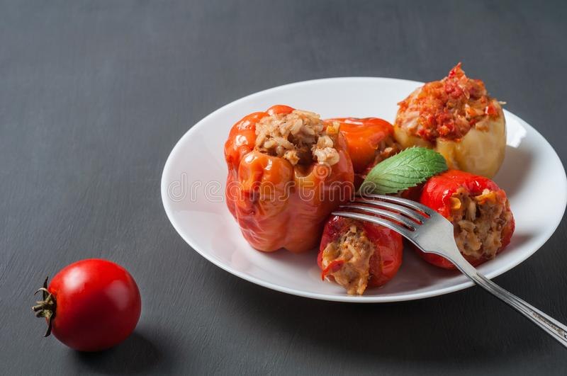 Portion of stuffed pepper, mint, on round white ceramic plate near metal fork, whole tomato lies on concrete table. Portion of stuffed pepper, mint, on round royalty free stock images