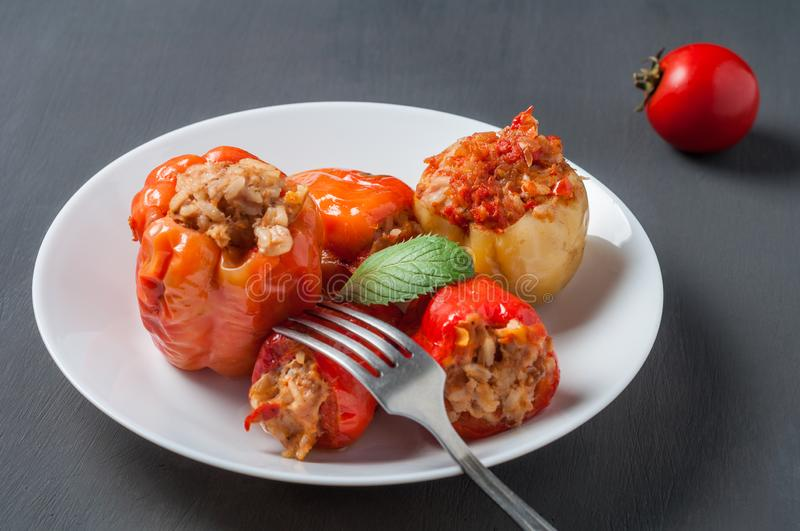 Portion of stuffed pepper, mint, on round white ceramic plate near metal fork, whole tomato lies on concrete table. Portion of stuffed pepper, mint, on round stock images