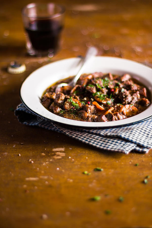 Portion of traditional irish beef and guinness beer stew with carrots and fresh parsley in a plate ready to serve. Selective focus stock photo