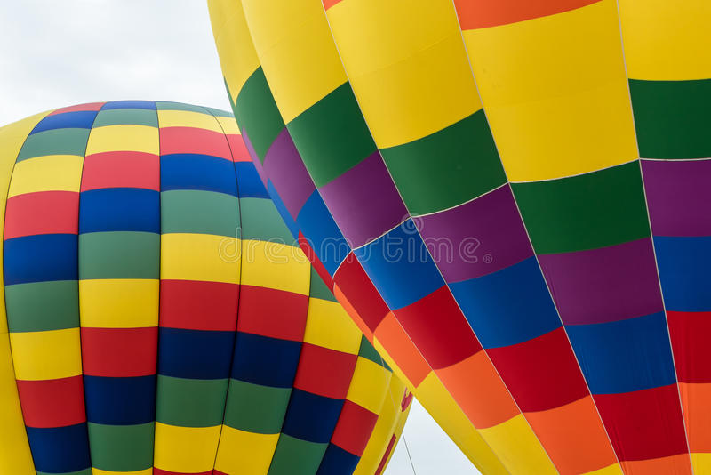 Portion of Two Hot Air Balloons. One Colorful Balloon in front of a second one against an almost white cloud filled sky stock photography